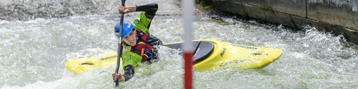 Drei Kajaker haben Spaß im künstlichen Wildwasser auf dem Eiskanal in Augsburg. Die Olympiastrecke von 1972 ist eine Herausforderung für jeden begeisterten Kajakfahrer.