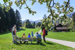 Familienwanderung im frühlingshaften Allgäu mit Schnee auf den Alpengipfeln und grünen saftigen Wiesen im Illertal, Maifeiertag an den Hängen der Hörnerkette.